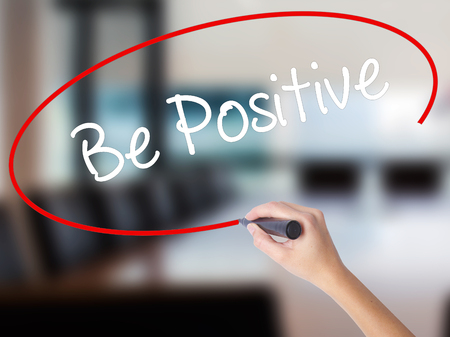 Woman Hand Writing Be Positive  with a marker over transparent board. Isolated on Office. Business concept. Stock Photo Stock Photo