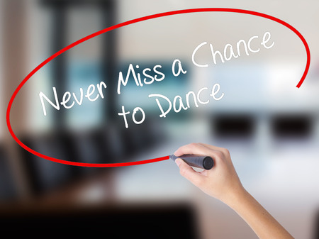 Woman Hand Writing Never Miss a Chance to Dance with a marker over transparent board. Isolated on Office. Business concept. Stock Photo Stock Photo