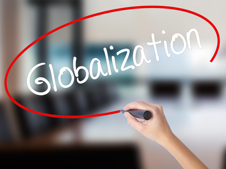 Woman Hand Writing Globalization with a marker over transparent board. Isolated on Office. Business concept. Stock Photo