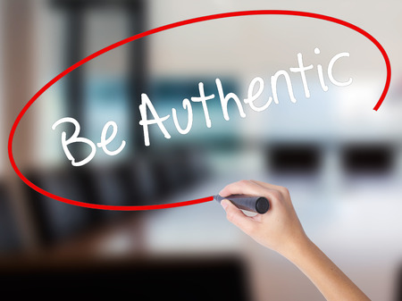 faked: Woman Hand Writing Be Authentic with a marker over transparent board. Isolated on Office. Business concept. Stock Photo