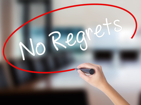 Woman Hand Writing No Regrets with a marker over transparent board. Isolated on Office. Business concept. Stock Photo