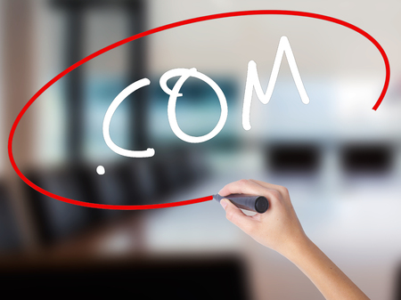Woman Hand Writing .COM with a marker over transparent board. Isolated on Office. Business concept. Stock Image