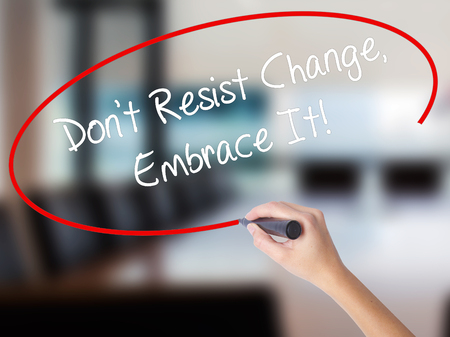 Woman Hand Writing Dont Resist Change, Embrace It! with a marker over transparent board. Isolated on Office. Business concept. Stock Photo