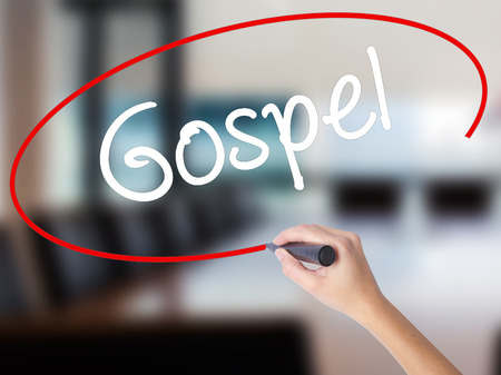 Woman Hand Writing Gospel  with a marker over transparent board. Isolated on Office. Business concept. Stock Photo