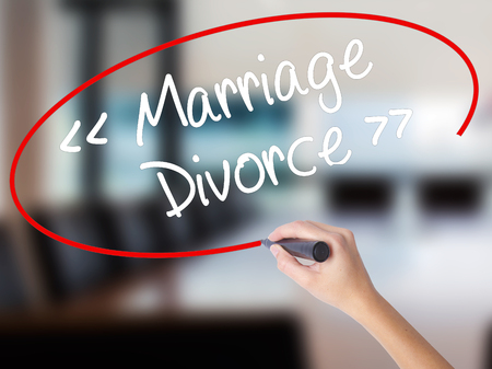 Woman Hand Writing Marriage - Divorce with a marker over transparent board. Isolated on Office. Business concept. Stock Photo