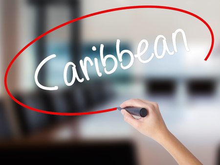 Woman Hand Writing Caribbean with a marker over transparent board. Isolated on Office. Business concept. Stock Photo