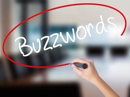 Woman Hand Writing Buzzwords with a marker over transparent board. Isolated on Office. Business concept. Stock Photo Stock Photo