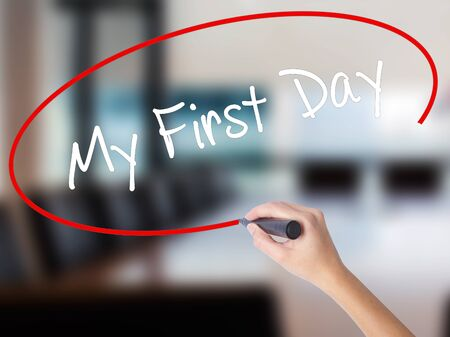 Woman Hand Writing My First Day with a marker over transparent board. Isolated on Office. Business concept. Stock Photo