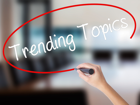 business trending: Woman Hand Writing Trending Topics with a marker over transparent board. Isolated on Office. Business concept. Stock Photo