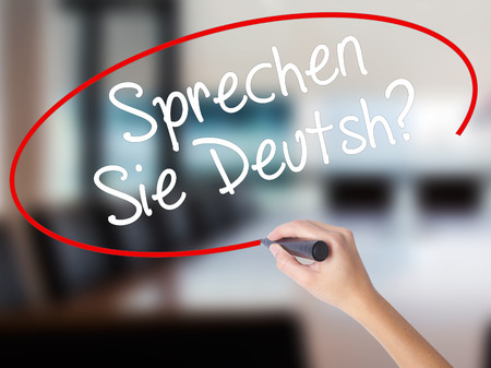 Woman Hand Writing Do You Speak German? (in German) with a marker over transparent board. Isolated on Office. Business concept. Stock Photo