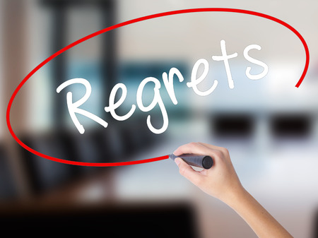 Woman Hand Writing  Regrets with a marker over transparent board. Isolated on Office. Business concept. Stock Photo