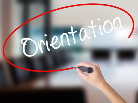 Woman Hand Writing Orientation with a marker over transparent board. Isolated on Office. Business concept. Stock Photo