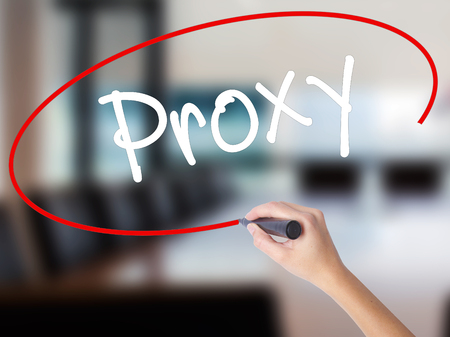 Woman Hand Writing Proxy with a marker over transparent board. Isolated on Office. Business concept. Stock Photo