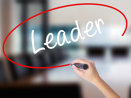 Woman Hand Writing Leader with a marker over transparent board. Isolated on Office. Business concept. Stock Photo