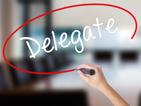 delegar: Woman Hand Writing Delegate with a marker over transparent board. Isolated on Office. Business concept. Stock Photo Foto de archivo