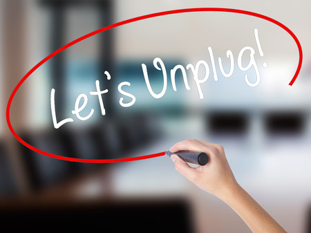 Woman Hand Writing Lets Unplug! with a marker over transparent board. Isolated on Office. Business concept. Stock Photo