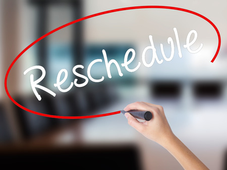 rescheduling: Woman Hand Writing Reschedule  with a marker over transparent board. Isolated on Office. Business concept. Stock Photo