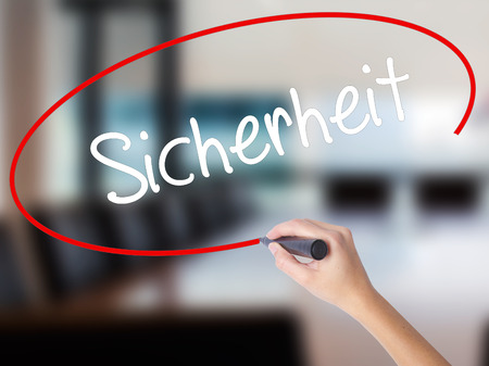 sicherheit: Woman Hand Writing Sicherheit (Safety in German) with a marker over transparent board. Isolated on Office. Business,  internet concept. Stock Photo