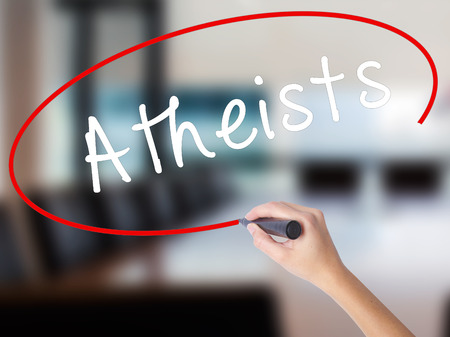 nonbelief: Woman Hand Writing Atheists with a marker over transparent board. Isolated on Office. Business concept. Stock Image
