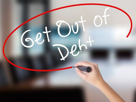 Woman Hand Writing Get Out of Debt with a marker over transparent board. Isolated on Office. Business concept. Stock Image