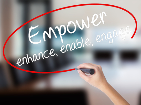 Woman Hand Writing Empower enhance, enable, engage with a marker over transparent board. Isolated on Office. Business concept. Stock Photo Stock Photo