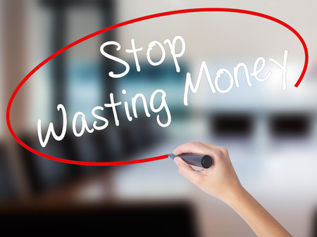 Woman Hand Writing Stop Wasting Money with a marker over transparent board. Isolated on Office. Business concept. Stock Photo