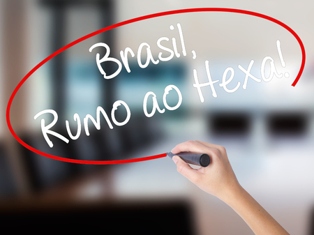Woman Hand Writing Brasil, Rumo ao Hexa! with a marker over transparent board. Isolated on Office. Business concept. Stock Photo