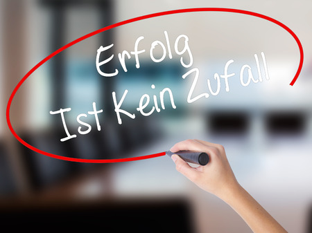 Woman Hand Writing Erfolg Ist Kein Zaufall (Success Is No Accident in German) with a marker over transparent board. Isolated on Office. Business concept. Stock Photo