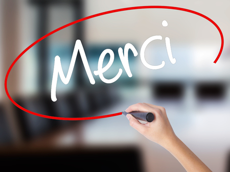 Woman Hand Writing Merci  (Thank You In French) with a marker over transparent board. Isolated on Office. Business concept. Stock Photo