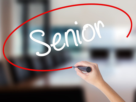 Woman Hand Writing Senior with a marker over transparent board. Isolated on Office. Business concept. Stock Photo Stock Photo
