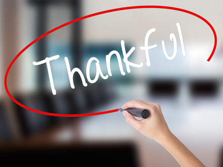 obliged: Woman Hand Writing Thankful  with a marker over transparent board. Isolated on Office. Business concept. Stock Photo