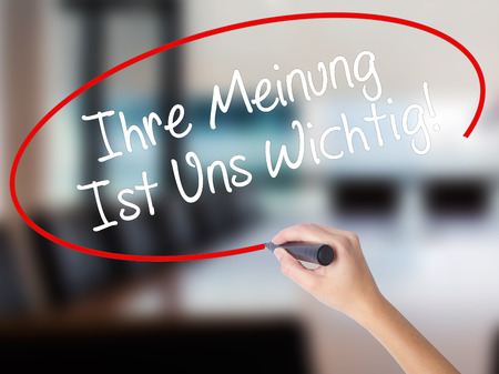 solicitation: Woman Hand Writing Ihre Meinung Ist Uns Wichtig! (Your Opinion is Important to Us in German) with marker on visual screen. Isolated on Office. Business concept. Stock Photo