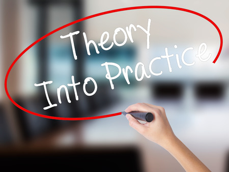 Woman Hand Writing Theory Into Practice with a marker over transparent board. Isolated on Office. Business concept. Stock Photo
