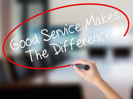 motto: Woman Hand Writing Good Service Makes The Difference with a marker over transparent board. Isolated on Office. Business concept. Stock Photo Stock Photo