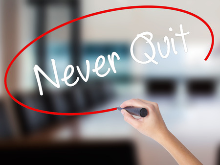Woman Hand Writing Never Quit with a marker over transparent board. Isolated on Office. Business concept. Stock  Photo Stock Photo