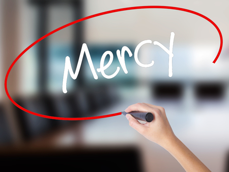 Woman Hand Writing Mercy with a marker over transparent board. Isolated on Office. Business concept. Stock Photo