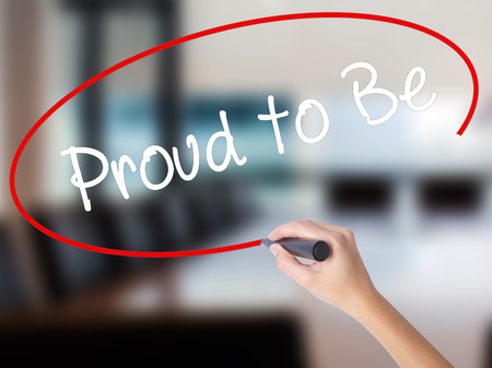 Woman Hand Writing Proud to Be with a marker over transparent board. Isolated on Office. Business concept. Stock Photo