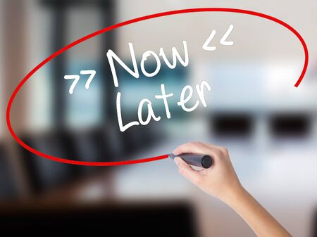 Woman Hand Writing NowLater with a marker over transparent board. Isolated on Office. Business concept. Stock Photo Stock Photo