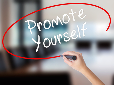 promote: Woman Hand Writing Promote Yourself with a marker over transparent board. Isolated on Office. Business concept. Stock Photo