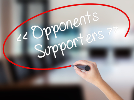 Woman Hand Writing Opponents - Supporters with a marker over transparent board. Isolated on Office. Business concept. Stock Photo