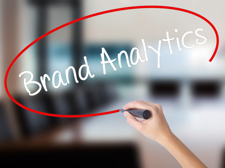 brand monitoring: Woman Hand Writing Brand Analytics with a marker over transparent board. Isolated on Office. Business concept. Stock Photo