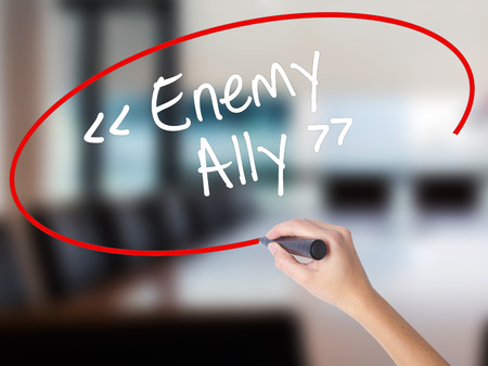 interdependence: Woman Hand Writing Enemy - Ally with a marker over transparent board. Isolated on Office. Business concept. Stock Photo