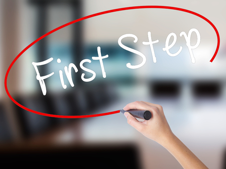 Woman Hand Writing First Step  with a marker over transparent board. Isolated on Office. Business concept. Stock Photo