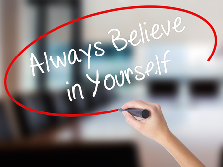 Woman Hand Writing Always Believe in Yourself with a marker over transparent board. Isolated on Office. Business concept. Stock Photo