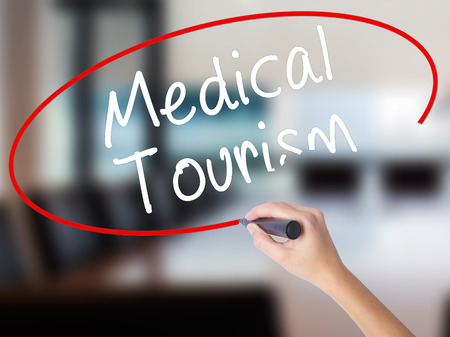 health care fees: Woman Hand Writing Medical Tourism with a marker over transparent board. Isolated on Office. Business concept. Stock Photo