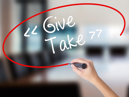 Woman Hand Writing Give - Take with a marker over transparent board. Isolated on Office. Business concept. Stock Photo