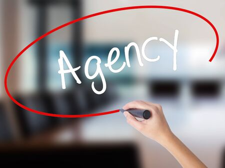 Woman Hand Writing Agency with a marker over transparent board. Isolated on Office. Business concept. Stock Photo