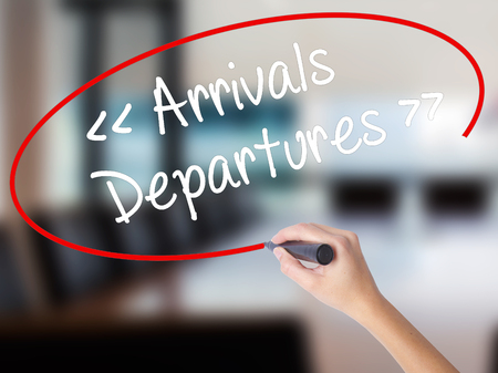 Woman Hand Writing Arrivals - Departures with a marker over transparent board. Isolated on Office. Business concept. Stock Photo