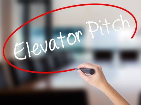 business pitch: Woman Hand Writing Elevator Pitch with a marker over transparent board. Isolated on Office. Business concept. Stock Photo