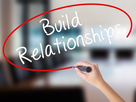 Woman Hand Writing Build Relationships with a marker over transparent board. Isolated on Office. Business concept. Stock Image